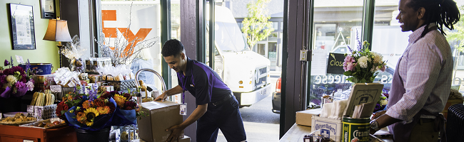 FedEx Ground driver delivering boxes to cafe