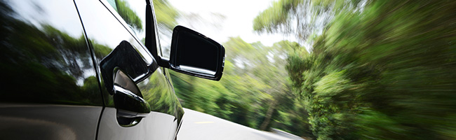 Rearview mirror on car driving down road