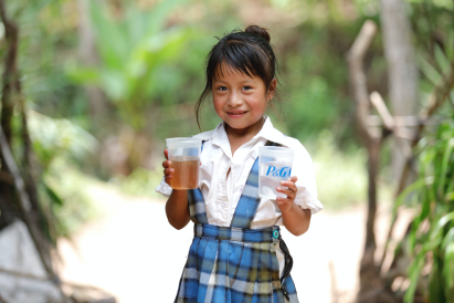little southeast asian girl holding 2 P&G branded plastic cups, 1 of tea and 1 of water.
