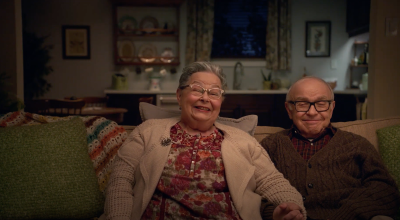 photo of an elderly couple sitting on a green couch smiling