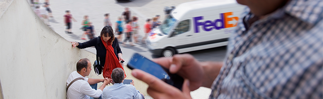 Person using smartphone with FedEx Express van in background